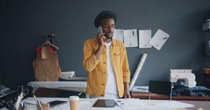 Diseñador creativo que hace llamada telefónica con el smartphone que habla en el trabajo metrajes