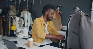 Diseñador creativo que mide la ropa hecha a mano en la sonrisa de goce simulada del trabajo almacen de metraje de vídeo