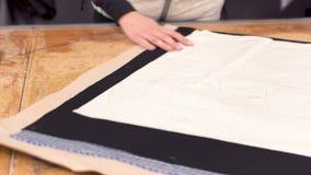 Diseñador de la modista que sujeta con grapa y que corta el modelo de la tela en la industria de ropa metrajes