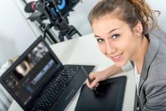 Diseñador de la mujer joven que usa la tableta de gráficos para corregir video fotos de archivo