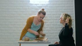 Diseñador de la mujer profesional que explica cómo hacer el sobre para el ayudante metrajes