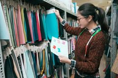 Diseñador de la mujer que elige la pañería de la muestra de la ropa Imagen de archivo libre de regalías