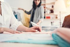 Diseñador de la ropa de dos jóvenes que trabaja en oficina de costura del diseño La empresaria cose la nueva ropa de la moda Pequ fotos de archivo