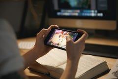 Diseñador de la señora que se sienta dentro en los juegos del juego de la noche fotos de archivo