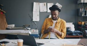 Diseñador de moda afroamericano que usa el smartphone que sonríe en el trabajo en estudio almacen de metraje de vídeo
