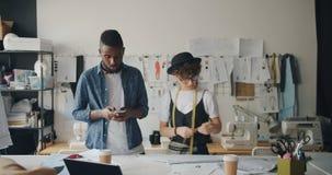Diseñador de moda afroamericano que usa smartphone cuando tela de medición de la muchacha almacen de video