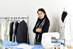 Diseñador de moda asiático que trabaja en su estudio de la sala de exposición, femenino en tienda de ropa de diseñador fotografía de archivo