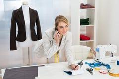 Diseñador de moda de sexo femenino que habla en el teléfono móvil foto de archivo libre de regalías