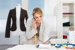 Diseñador de moda de sexo femenino que habla en el teléfono móvil fotos de archivo libres de regalías