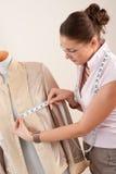 Diseñador de moda de sexo femenino que toma la medida foto de archivo
