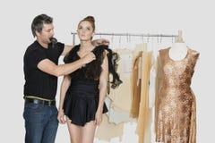 Diseñador de moda de sexo masculino maduro que ajusta el vestido en modelo en estudio del diseño fotos de archivo