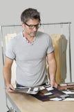 Diseñador de moda de sexo masculino maduro que mira muestras del paño Fotografía de archivo libre de regalías