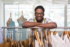 Diseñador de moda de sexo masculino que se inclina en el estante de la ropa imagen de archivo