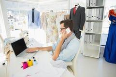 Diseñador de moda de sexo masculino que usa el ordenador portátil y el teléfono móvil Imagen de archivo