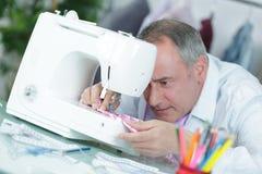 Diseñador de moda de la Edad Media que cose con la máquina de coser Foto de archivo libre de regalías