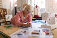 Diseñador de moda mayor confiado en su taller Foto de archivo libre de regalías