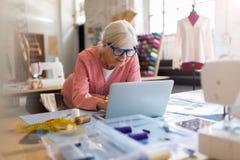 Diseñador de moda mayor confiado en su taller Imagen de archivo libre de regalías