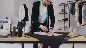 Diseñador de moda o sastre que hace un modelo en un pedazo marrón de tejido La modista está utilizando una tiza, llevando a cabo  almacen de metraje de vídeo
