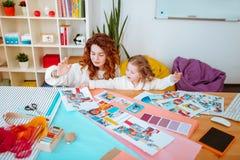 Diseñador de moda que mira las fotos de los modelos que entretienen a poca hija fotos de archivo libres de regalías