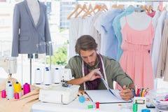 Diseñador de moda que se sienta detrás de un escritorio Imágenes de archivo libres de regalías