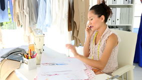 Diseñador de moda que se sienta en la tabla que habla en el teléfono