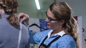 Diseñador de moda que toma medidas del cliente metrajes