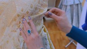 Diseñador de moda que trabaja con el vestido de la adaptación del modelo nuevo en maniquí metrajes