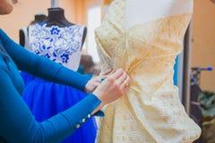 Diseñador de moda que trabaja con el vestido de la adaptación del modelo nuevo en maniquí foto de archivo libre de regalías