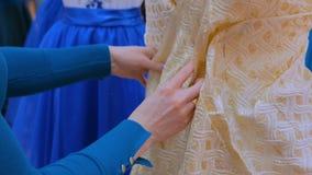 Diseñador de moda que trabaja con el vestido de la adaptación del modelo nuevo en maniquí almacen de metraje de vídeo