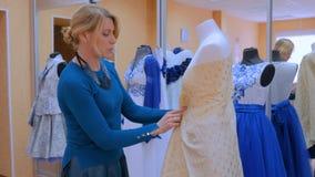 Diseñador de moda que trabaja con el vestido de la adaptación del modelo nuevo en maniquí almacen de video