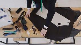 Diseñador de moda que trabaja con la tela en el estudio por completo de las herramientas de la adaptación Modelo, tijeras, cinta  almacen de metraje de vídeo