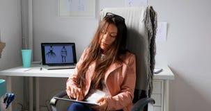 Diseñador de moda que usa la tableta digital en el estudio 4k del diseño almacen de video