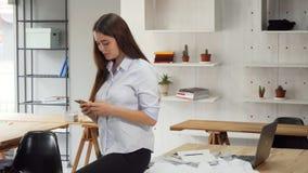 Diseñador de moda de sexo femenino atractivo que se relaja después del trabajo, mandando un SMS en su teléfono elegante almacen de video