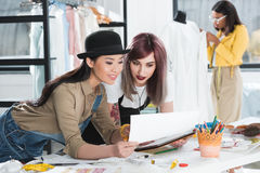Diseñador de moda sonriente que trabaja con bosquejos y la tableta digital Fotografía de archivo