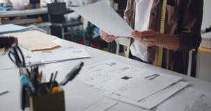 Diseñador de ropa que sostiene dibujos de la ropa que trabaja en el estudio que crea la ropa almacen de metraje de vídeo