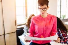 Diseñador de sexo femenino atractivo joven que mira esquema del proyecto foto de archivo