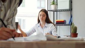 Diseñador de sexo femenino atractivo que contesta al teléfono en la oficina almacen de metraje de vídeo