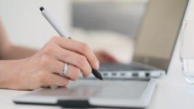 Diseñador de sexo femenino blanco joven que trabaja en un ordenador portátil usando una tableta gráfica de la pluma almacen de video