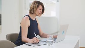 Diseñador de sexo femenino blanco joven que trabaja en un ordenador portátil usando una tableta gráfica de la pluma almacen de metraje de vídeo
