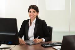 Diseñador de sexo femenino con la tableta gráfica en el escritorio imagen de archivo