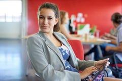 Diseñador de sexo femenino confiado que trabaja en una tableta digital en espacio de oficina creativo rojo Imagen de archivo libre de regalías