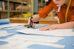 Diseñador de sexo femenino hermoso elegante que usa las tijeras Fotografía de archivo