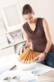 Diseñador de sexo femenino joven con muestras de madera del color Fotografía de archivo