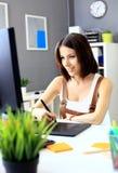 Diseñador de sexo femenino joven que usa la tableta de gráficos mientras que trabaja imagen de archivo