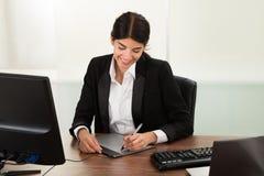 Diseñador de sexo femenino que usa la tableta gráfica foto de archivo