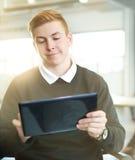 Diseñador de sexo masculino confiado que trabaja en una tableta digital en espacio de oficina creativo rojo Fotos de archivo