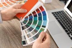 Diseñador de sexo masculino que trabaja con la paleta de colores en la tabla de la oficina fotos de archivo libres de regalías
