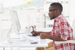 Diseñador enfocado que usa el digitizador y el ordenador Imagen de archivo libre de regalías