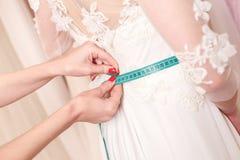Diseñador experto que cabe el vestido nupcial a la muchacha Foto de archivo