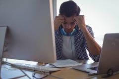 Diseñador gráfico confuso que se sienta en oficina imagenes de archivo